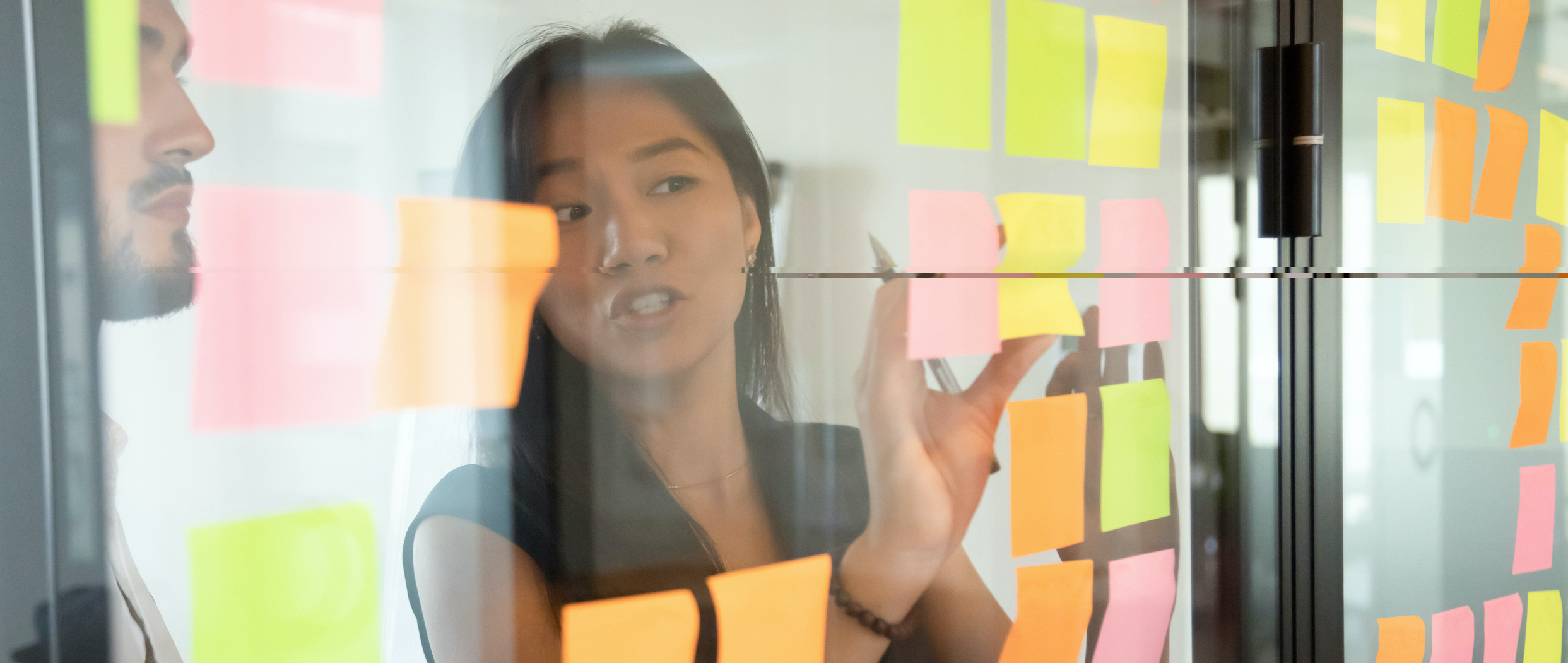 Two people looking at a collection of post-it notes