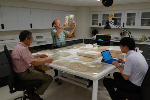 Professor Thomas Conlan observes documents in PUL's Conservation Lab