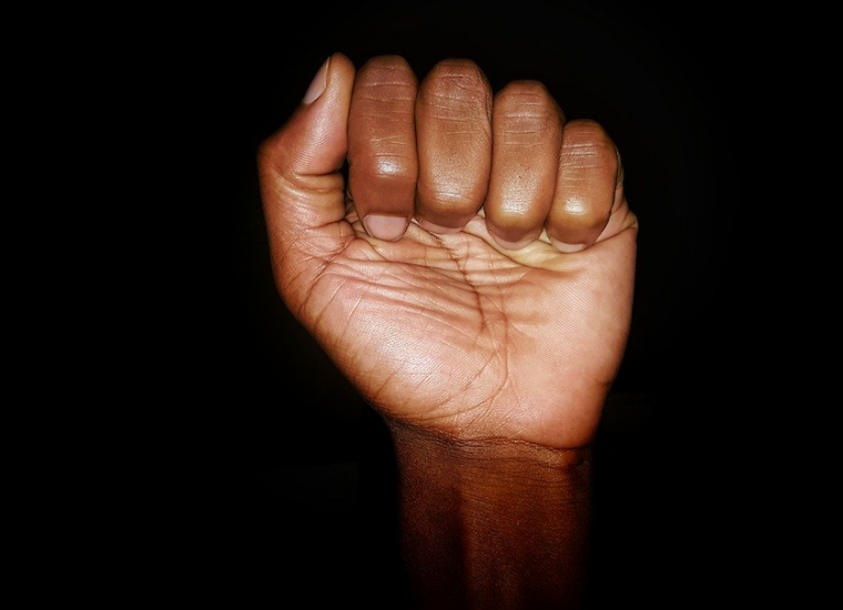 Black person's fist against black background