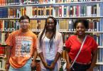 Three students interning this summer, in front of shelves in Firestone Library